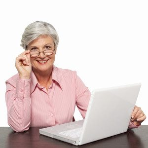 woman with gray hair and glasses using a computer