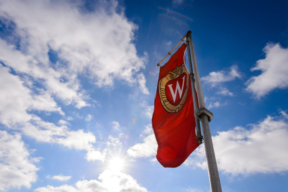 Wisconsin flag flying in sky with puffy clouds