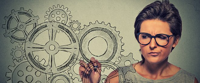 woman looking puzzled drawing gears on glass