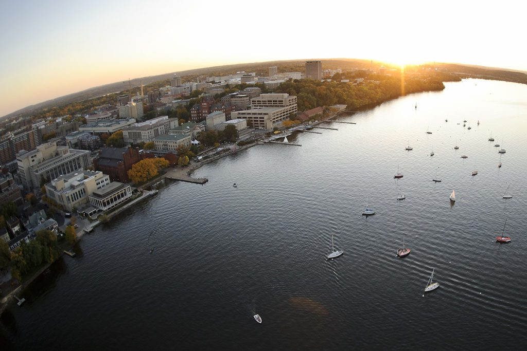 Boats dot Lake Mendota in a fisheye-lens aerial view of the University of Wisconsin-Madison campus during an autumn sunset.