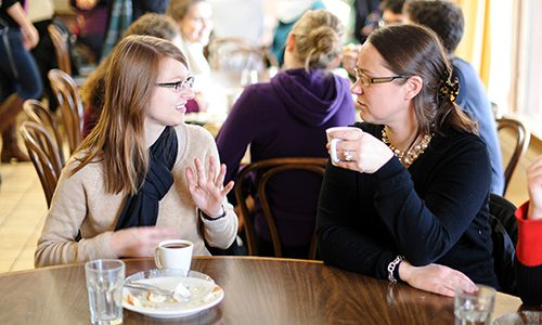two women drink coffee at the UW-Madison French House