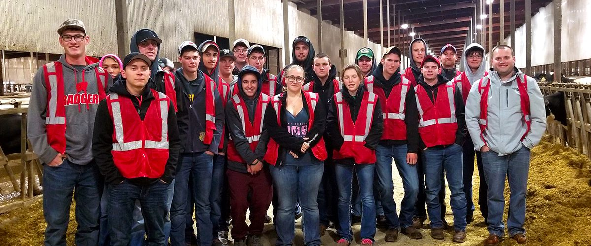 Farm and Industry Short Course students stand in the cow barn as a group